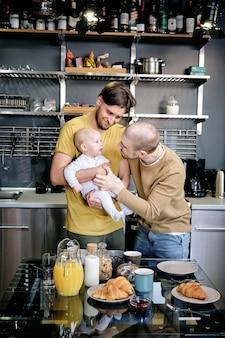 Due gay allegri che giocano con un neonato in cucina