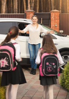 Due ragazze allegre che corrono dalla madre incontrandole dopo la scuola