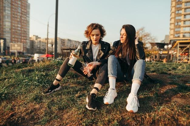 Due ragazze allegre in vestiti alla moda che si siedono sull'erba su uno sfondo di paesaggio urbano al tramonto