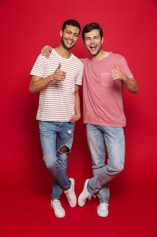 Due amici allegri degli uomini che stanno isolati sopra la parete rossa, mostrando i pollici in su