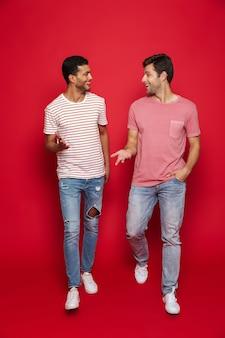 Due amici allegri degli uomini che camminano isolati sopra la parete rossa