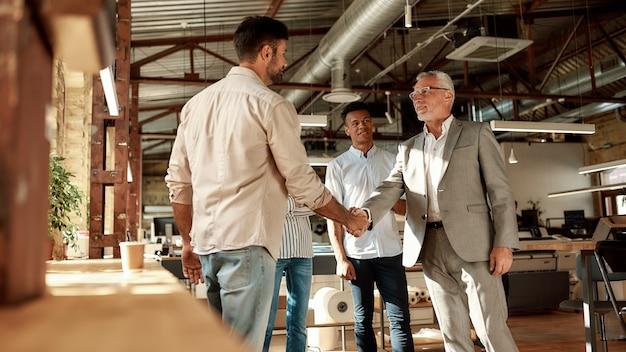 Due uomini allegri che si stringono la mano e sorridono mentre sono in piedi con i colleghi nell'ufficio moderno