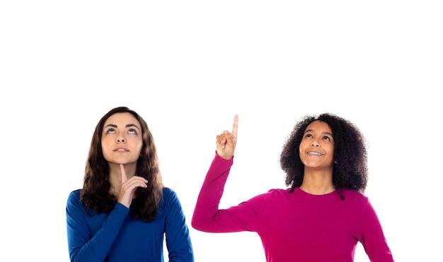 Due ragazze allegre degli amici delle donne isolate su una priorità bassa bianca