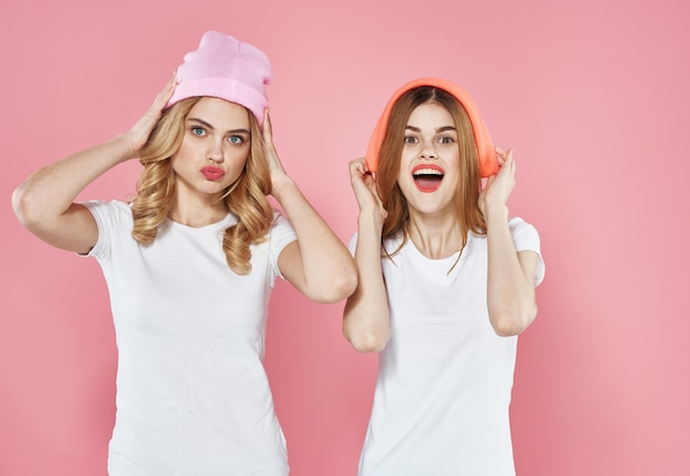 Due donne allegre cappello rosa vestiti alla moda tendenza stile di vita isolato sullo sfondo