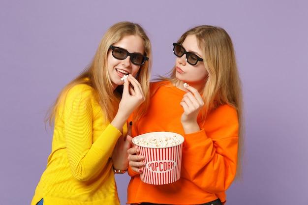 Due giovani sorelle gemelle bionde allegre in occhiali 3d imax che guardano film, tengono il popcorn isolato sulla parete blu viola pastello concetto di stile di vita familiare di persone.