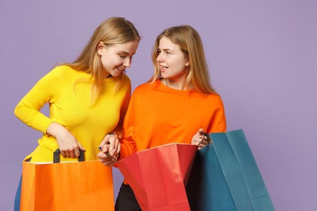 Due giovani sorelle gemelle bionde allegre in abiti vivaci tengono il pacchetto con gli acquisti dopo lo shopping isolato sulla parete blu viola. concetto di stile di vita familiare di persone.