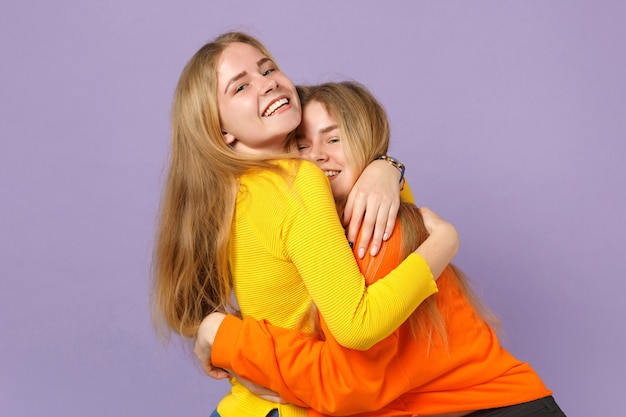 Due giovani sorelle gemelle bionde allegre in abiti colorati vividi che abbracciano e isolate sulla parete blu viola pastello. concetto di stile di vita familiare di persone.