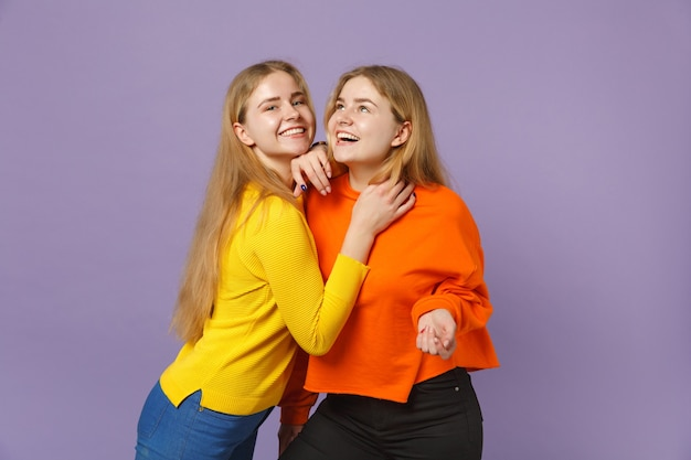 Due giovani sorelle gemelle bionde allegre in abiti colorati vivaci in piedi e abbracciate isolate sulla parete blu viola pastello concetto di stile di vita familiare di persone.