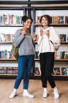 Due studentesse allegre che studiano in biblioteca, portando zaini