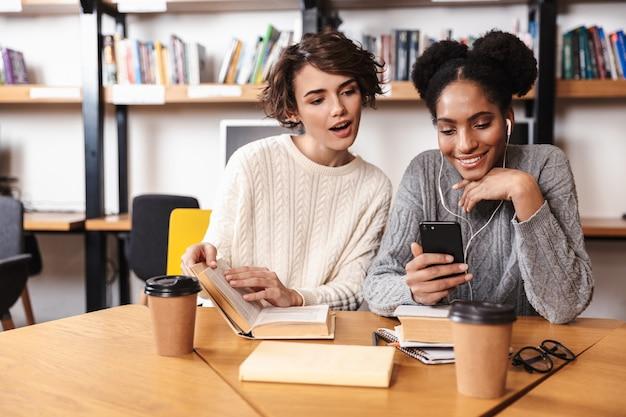 Due allegre ragazze giovani studenti che studiano in biblioteca, tenendo il telefono cellulare,