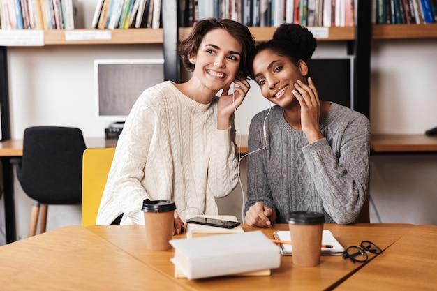 Due studentesse allegre che studiano in biblioteca, ascoltando musica con gli auricolari