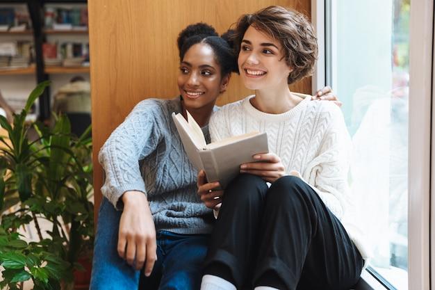 Due studentesse allegre che studiano in biblioteca, leggendo un libro insieme