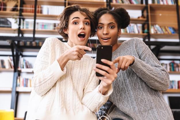 Due studentesse allegre che studiano in biblioteca, utilizzando il telefono cellulare, indossando gli auricolari