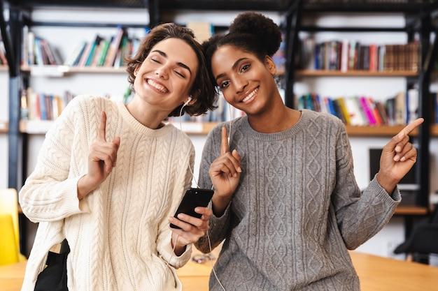 Due studentesse allegre che studiano in biblioteca