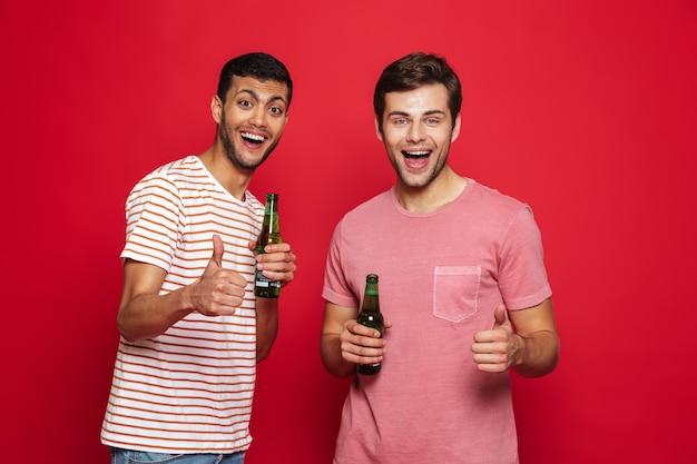 Due allegri giovani uomini in piedi isolato sopra il muro rosso, bere acqua di soda dalle bottiglie, pollice in alto