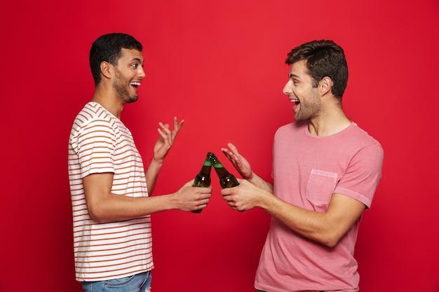 Due giovani allegri in piedi isolato sopra il muro rosso, bevendo acqua di soda dalle bottiglie
