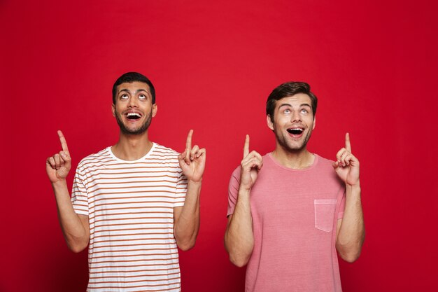 Due giovani allegri in piedi isolato sopra la parete rossa, indicando lo spazio della copia