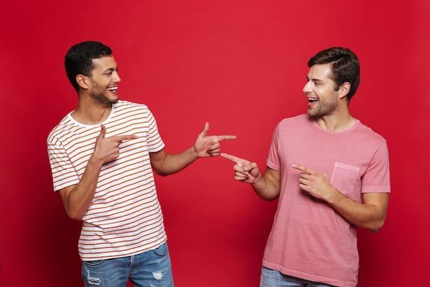 Due giovani allegri che stanno isolati sopra la parete rossa, indicanti l'un l'altro