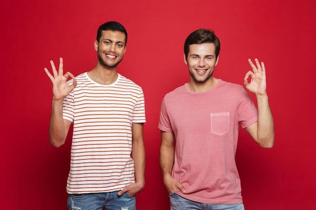 Due giovani allegri che stanno isolati sopra la parete rossa, mostrando ok