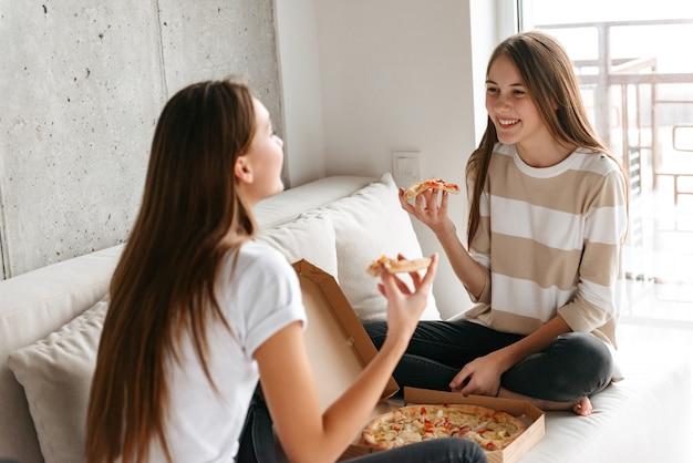 Due allegre giovani ragazze adolescenti parlando seduti su un divano a casa, mangiando pizza