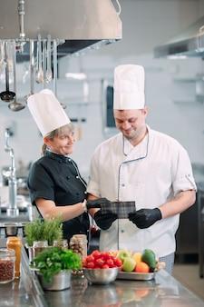 Due cuochi discutono del menu nella cucina di un ristorante