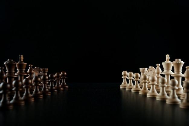Due eserciti di scacchi su uno sfondo nero faccia a faccia