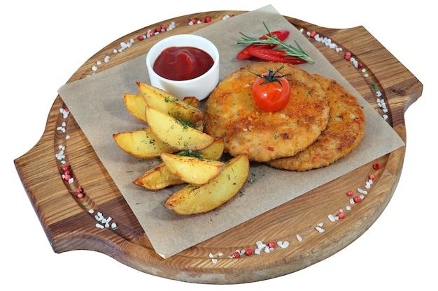 Cotoletta di pollo due con un contorno di fette di patate fritte su una tavola di legno circolare che serve, isolato su sfondo bianco.