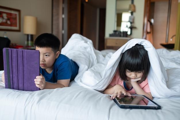 Due bambini dipendenti tablet, ragazzo asiatico guardando il fumetto