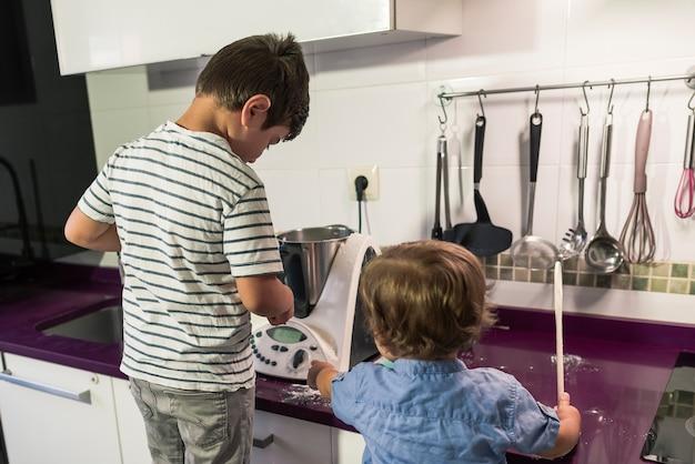 Due bambini che cuociono la torta a casa.