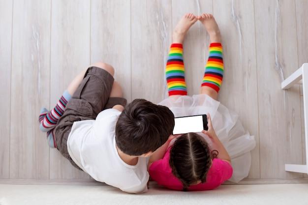 Due bambini, ragazzo e ragazza, sono seduti per terra contro il muro, gambe in calzini lunghi a righe luminose e giocano su uno smartphone. vista dall'alto. focus selettivo.