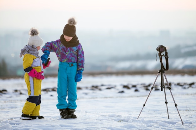 Due bambini ragazzo e ragazza divertirsi fuori in inverno giocando con la macchina fotografica su un treppiede sul campo coperto di neve.