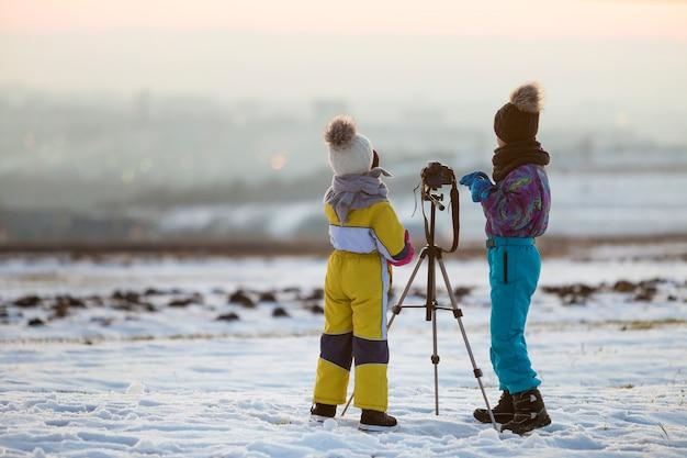 Due bambini ragazzo e ragazza divertirsi fuori in inverno giocando con la macchina fotografica