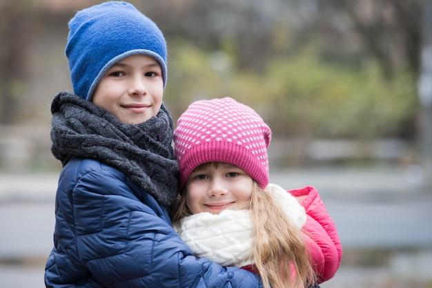 Un ragazzo e una ragazza di due bambini che si abbracciano all'aperto che porta i vestiti caldi in autunno freddo o tempo di inverno.