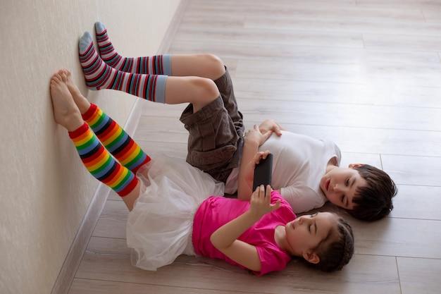 Due bambini, fratello e sorella, sono sdraiati sul pavimento e giocano su uno smartphone