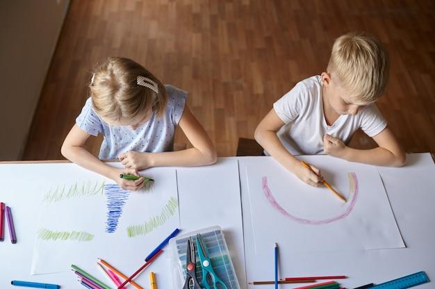 Due bambini che disegnano al tavolo, vista dall'alto