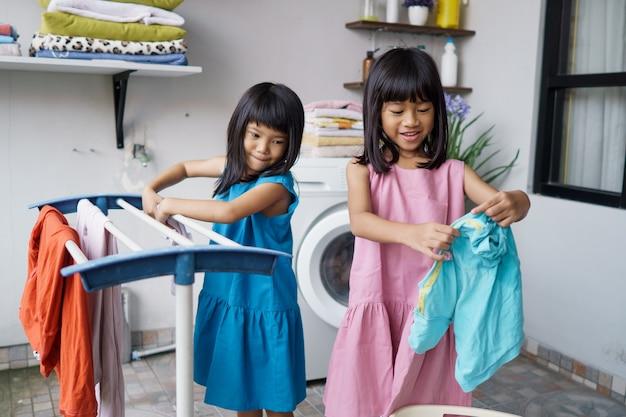 Due bambini che si divertono bambina felice a lavare i vestiti e ride nella lavanderia