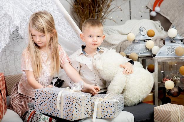 Due bambini sorridono tra scatole regalo di natale in una casa decorata.buon natale e buone feste!