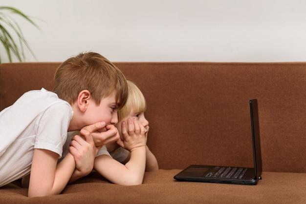 Due bambini si trovano sul divano e fissano il monitor del laptop. film per bambini