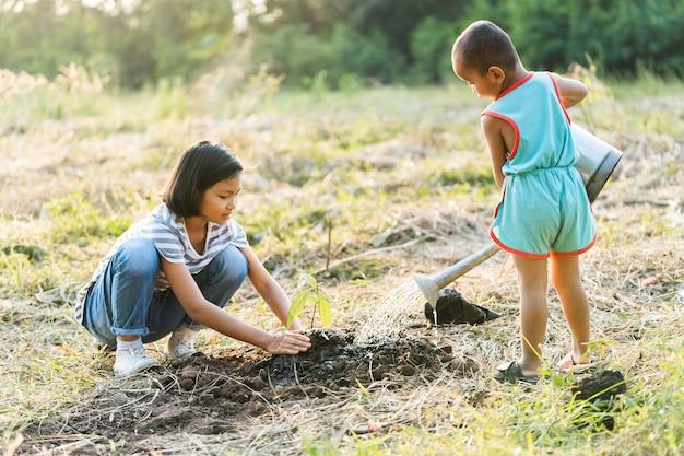 Due bambini che piantano alberi. concetto di ambiente eco