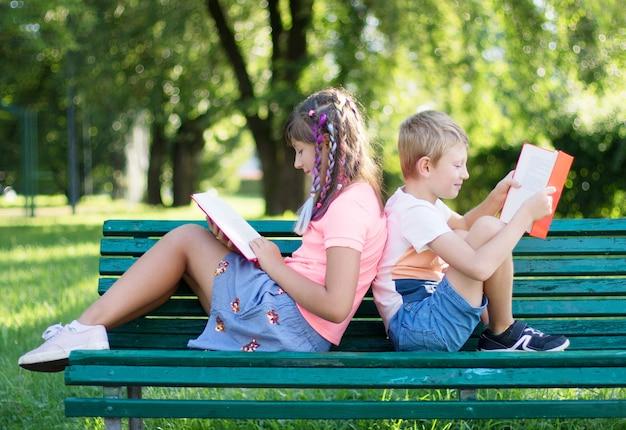 Due bambini seduti su una panchina stanno leggendo un libro al parco