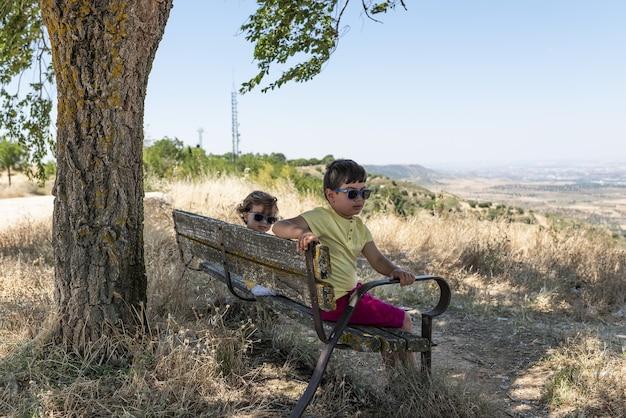 Due bambini seduti in un gazebo di campo che guardano la natura