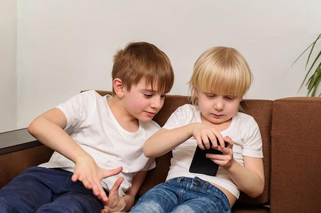 Due bambini usano il telefono. concetto di dipendenza da bambini e gadget.