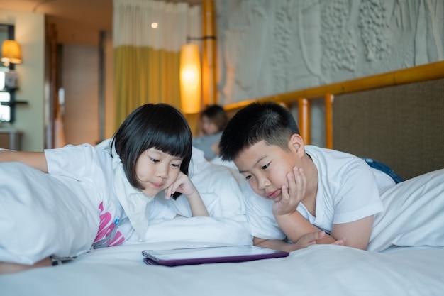 Tablet dipendente da due bambini cinesi, bambino asiatico che guarda il telefono insieme sul loro letto