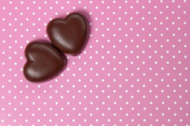 Due cioccolatini cuore su sfondo rosa con pois, san valentino, da vicino con copia spazio