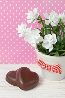 Due cioccolatini cuore e piccolo fiore in vaso con fiocco rosso su fondo di legno bianco con pois, giorno di san valentino, da vicino con spazio di copia