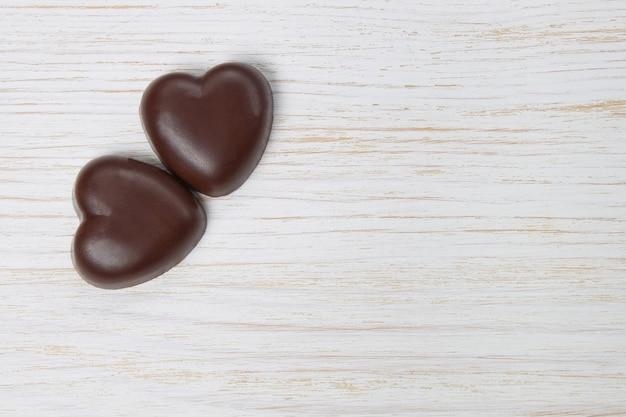 Due cioccolatini cuore bianco su sfondo di legno con pois, giorno di san valentino, da vicino con copia spazio