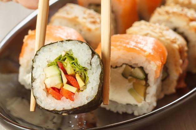 Due bacchette che tengono hosomaki con verdure e diversi involtini di sushi con frutti di mare su un piatto di ceramica sullo sfondo. cucina giapponese. profondità di campo. focus sul rotolo con le bacchette
