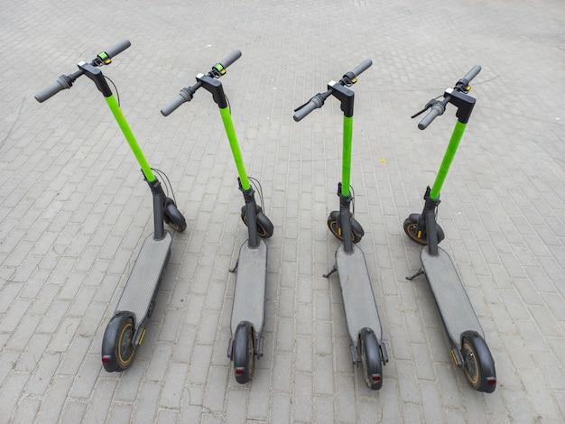 Due scooter da città sull'asfalto. quattro scooter parcheggiati nella città estiva. moderno mezzo di trasporto giovanile. vista dall'alto.