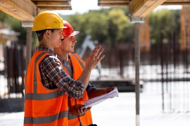 Due ingegneri civili vestiti con giubbotti e caschi da lavoro arancioni discutono del processo di costruzione in cantiere vicino alle costruzioni in legno e ai telai in acciaio.