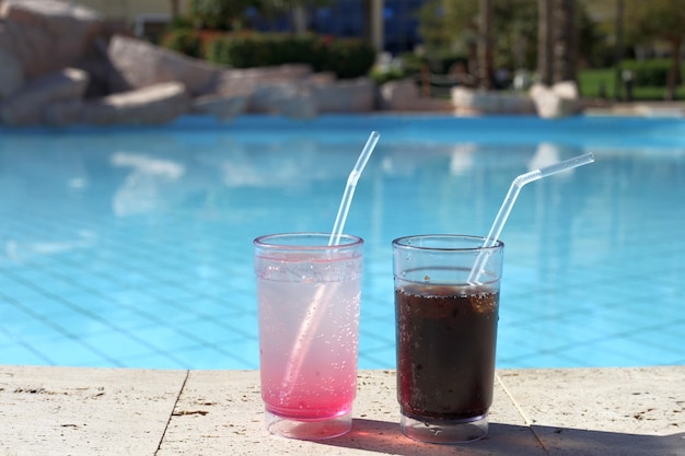 Due bicchieri da cocktail da un'acqua blu della piscina. vacanze estive
